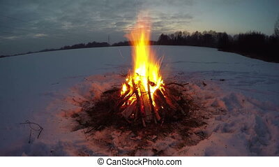 Bonfire burning in the snowy field - Bonfire campfire...