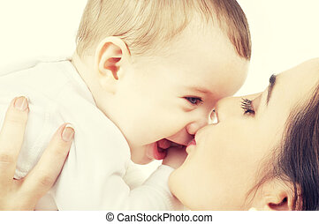 mother kissing her baby - family and happy people concept -...