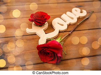 close up of word love cutout with red rose on wood