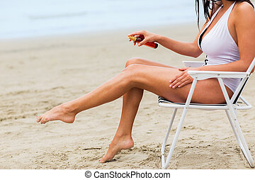close up of woman sunbathing on beach - summer vacation,...