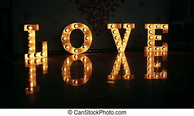 Word love consisting of lights on glossy floor - Word love...