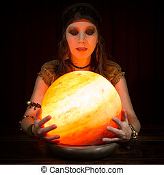Young pretty fortune teller with a crystal ball, dark...