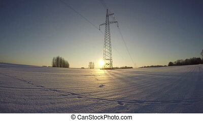 field with electrical pylon winter - Sunset in the field...