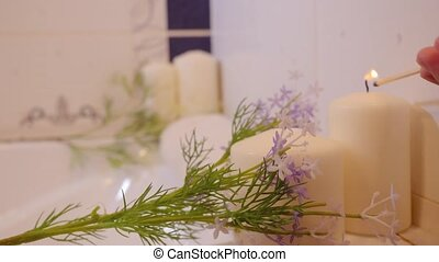 Women hand burns candles in bathroom Spa still life...