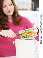 Woman Scraping Vegetable Peelings Into Recycling Bin