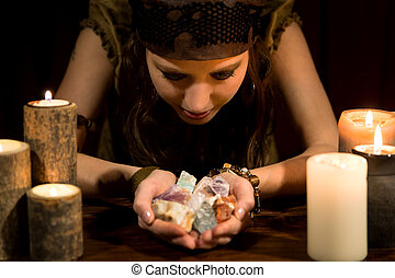 Psychic with a lots of healing stones - young female psychic...