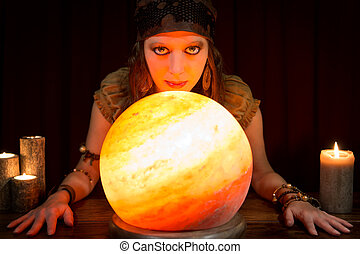 young pretty fortune teller with a shining crystal ball and...