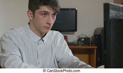 Programmer coding at two computers - Handsome young...
