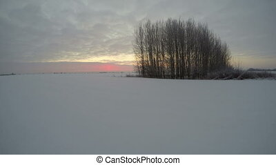 Sunrise in snow covered field on cloudy winter day, time...