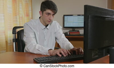 Outsourcing helping hand typing - Young handsome programmer...
