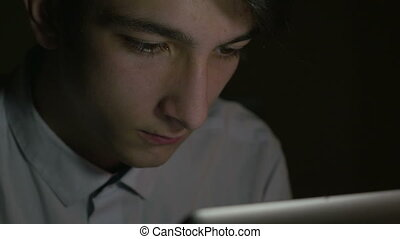Close-up of young man using tablet