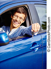 Guy in car with key - Young hispanic man wearing glasses and...
