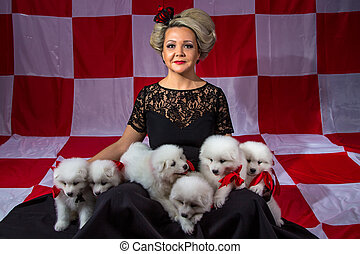Happy woman with white little puppies on plaid background