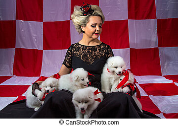 Blond woman in crown with fluffy puppies on plaid background