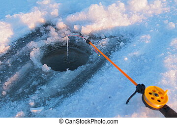 ice-hole and fishing tackle fishing line in focus