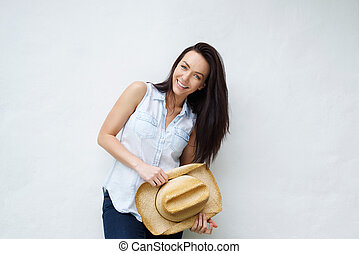 Smiling woman holding cowboy hat