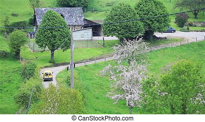 Car moving down the provincial road among green trees and...