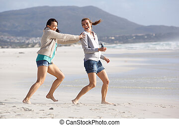 Two female friends playing on the beach
