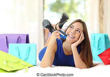 Girl holding a credit card thinking what to buy at home -...