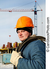 construction worker in front of building site at winter