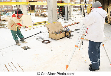 Land surveyor and assistant working with theodolite equipment at a construction site in winter