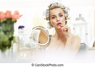 Portrait of a delicate blond woman in a make up room
