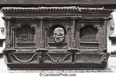 very old carved window and mask on it in Kathmandu, Nepal