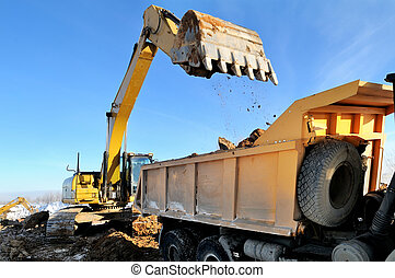 loader excavator loading earth to body of rear-end tipper -...
