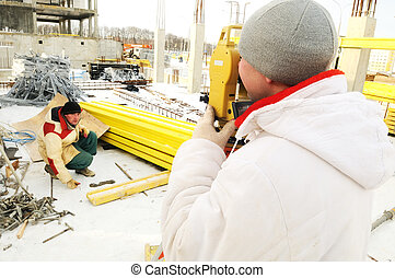 Land surveyor working with theodolite equipment at a construction site in winter