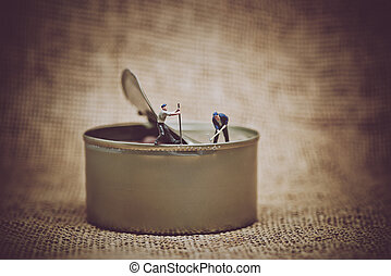 Miniature workers opening a can. Color tone tuned photo.