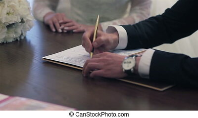 Newlyweds sign marriage certificate - Bride and groom...