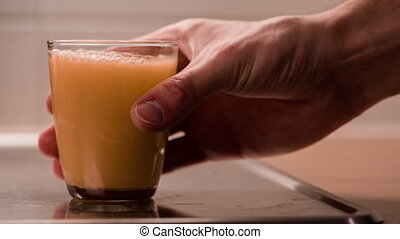 Hand takes a glass with juice then puts it already...