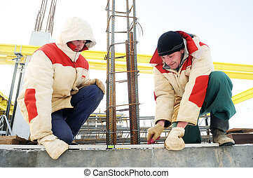 workers using leveling instrument at construction site - two...