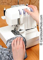 sewing on the machine - two woman hands sewing on the...