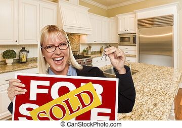 Young Woman Holding Sold Sign and Keys Inside New Kitchen