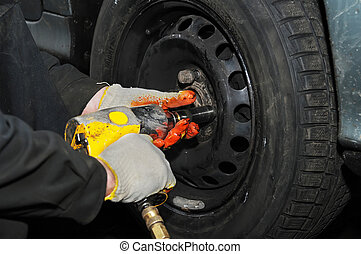 tyre fitting with air compressed wrench - two hands making...