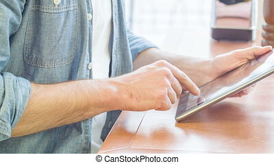 Man using his portable tablet at the restaurant. - Digital...