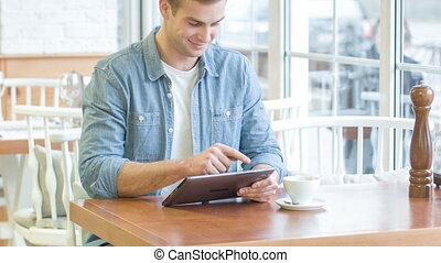 Young pleasant man using his digital tablet - Man with his...