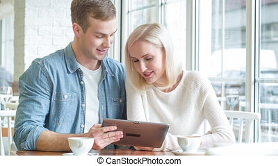 Young couple is busy with tablet at the restaurant. - Couple...