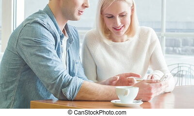 Young couple is discussing something over the smartphone. -...