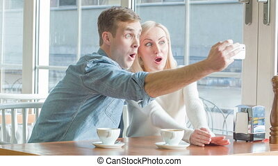 Young couple is taking selfies at the restaurant - Joyful...