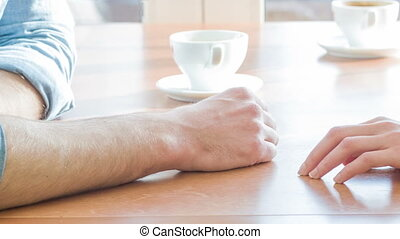 Young couple holding each other hands at the restaurant. -...