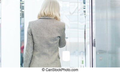 Female executive on her way to another floor. - Busy day....