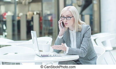 Exasperated businesswoman talking on the phone. - Facing...