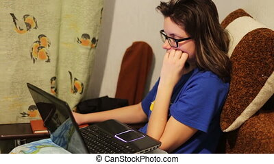 Tired student girl working at a laptop at home.