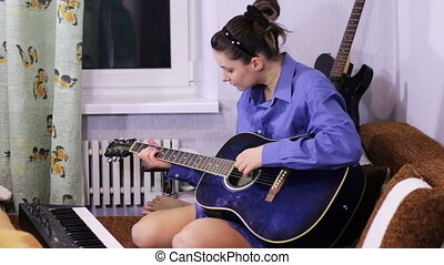 Young beautiful girl learning to play the guitar at home. -...