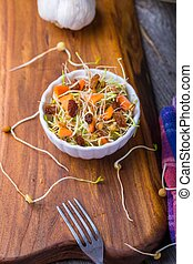 Fresh lentil and wheat sprouts salad with carrot, raisins, olive and garlic