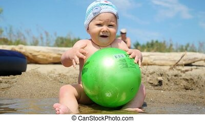 Cute baby boy playing with a ball on the beach 1920x1080
