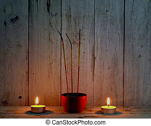 incecse sticks with candle flame on wooden background,pray...