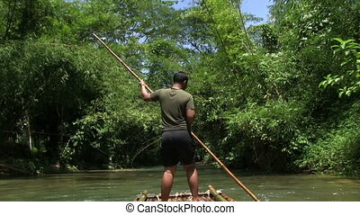 Tropical River In The Jungle - rafting on a bamboo raft on a...